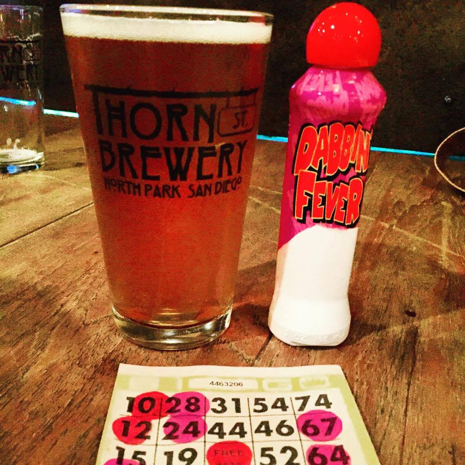 A pint glass full of beer, with thorn street brewery logo, next to a bingo dabber and a bingo card